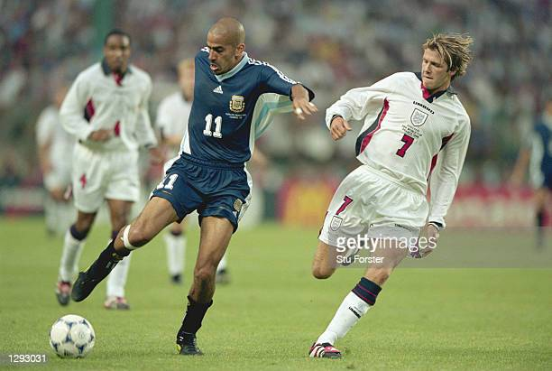 Juan Sebastian Veron of Argentina takes on David Beckham of England during the World Cup second round match at the Stade Geoffroy Guichard in St...