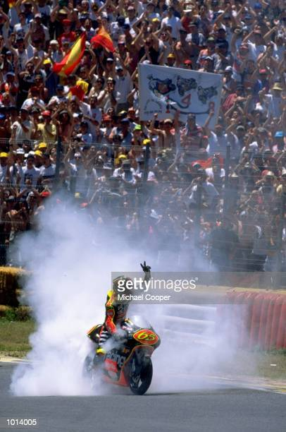 Loris Capirossi of Italy celebrates with a burnout on his Aprilia after finishing in third place during the Madrid Motorcycle Grand Prix at the...