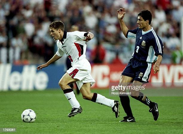 Michael Owen of England shrugs off Jose Chamot of Argentina on his way to goal during the World Cup second round match at the Stade Geoffroy Guichard...