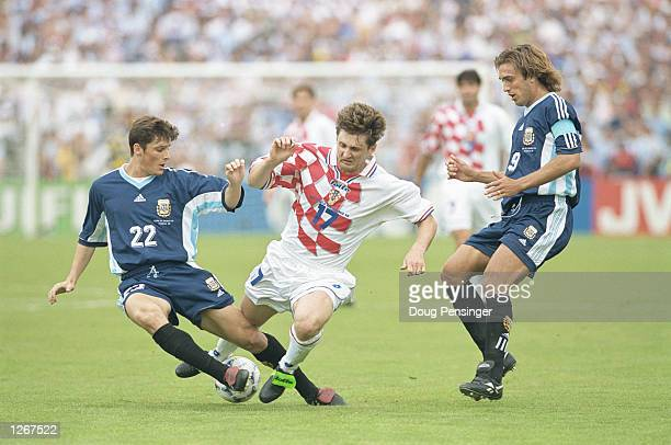 Robert Jarni of Croatia is tackled by Javier Zanetti of Argentina as Gabriel Batistuta looks on during the World Cup group H game at the Parc Lescure...