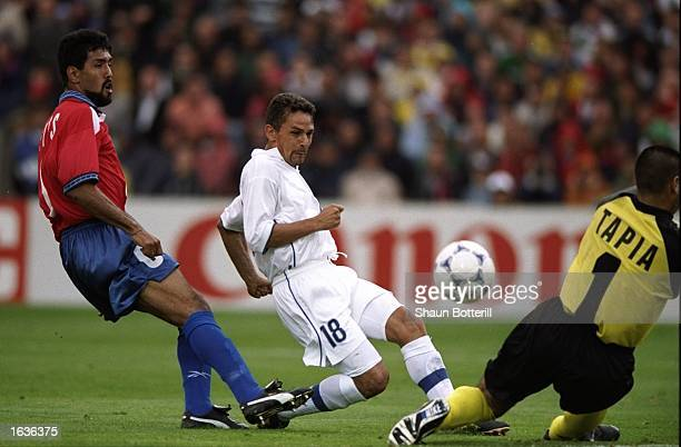 Roberto Baggio of Italy beats Pedro Reyes of Chile and tries to chip the onrushing Chile goalkeeper Nelson Tapia during the World Cup group B game at...