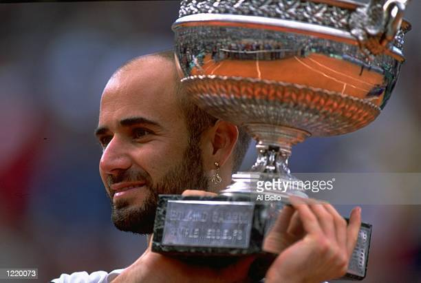 Andre Agassi of the United States celebrates victory with the trophy during the 1999 French Open Final match against Andrei Medvedev of the Ukraine...