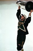 Mike Modano of the Dallas Stars carries the Stanley Cup on the ice after the Stanley Cup game against the Buffalo Sabres at the Marine Midland Arena...