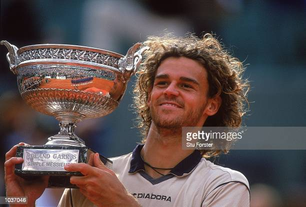 Gustavo Kuerten of Brazil poses with the trophy after winning the mens singles final match against Magnus Norman of Sweden at the French Open at...