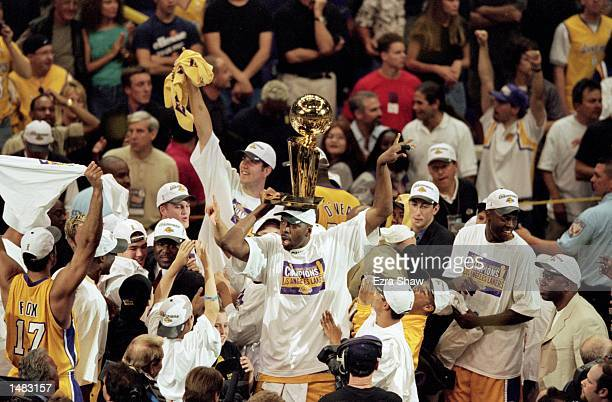 John Salley of the Los Angeles Lakers holds the NBA championship trophy on his head after winning the NBA Finals Game 6 against the Indiana Pacers at...