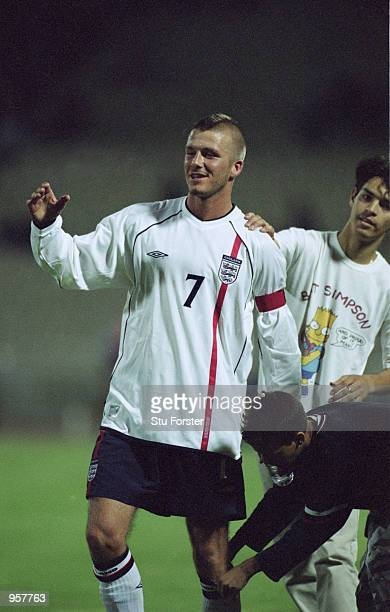 A fan tries to remove David Beckham of England sock to keep as a souvenir after the World Cup 2002 Group Nine Qualification match against Greece...