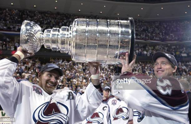 Ray Bourque of the Colorado Avalanche and teammate Patrick Roy raise the Stanley Cup after they beat the New Jersey Devils 31 in game seven of the...