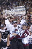 Ray Bourque of the Colorado Avalanche lifts the cup as teammate Joe Sakic hugs after the Colorado Avalanche defeated the New Jersey Devils 31 in game...