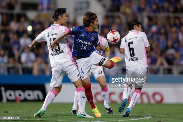 Jun Amano of Yokohama FMarinos controls the ball under pressure of Jung Seung Hyun and Akito Fukuta of Sagan Tosu during the JLeague J1 match between...