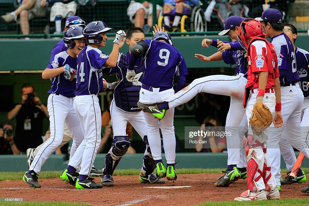 Jun Ha Yoo #9 of Team Asia-Pacific celebrates after hitting a two RBI home run against Team Japan during fifth inning of the International Championship game of the Little League World Series at Lamade Stadium on August 23, 2014 in South Williamsport, Pennsylvania. Team Asia-Pacific defeated Team Japan 12-3.