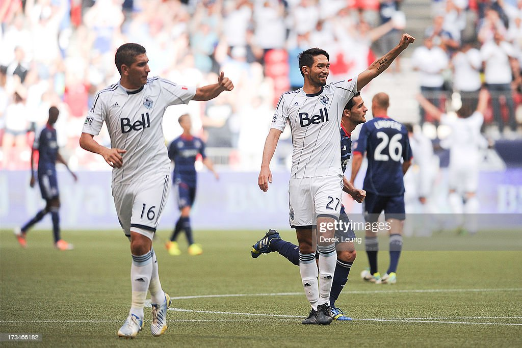 Jun Marques Davidson #27 and Johnny Leveron #16 of the Vancouver Whitecaps celebrate the Whitecaps' first goal scored by their teammate Camilo Sanvezzo #7 (not pictured) against Chicago Fire during an MLS Match at B.C. Place on July 14, 2013 in Vancouver, British Columbia, Canada.