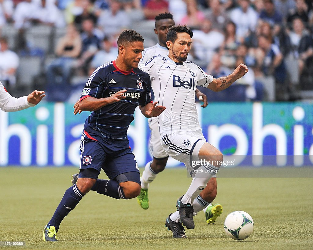 Jun Marques Davidson #27 of the Vancouver Whitecaps dribbles the ball past Quincy Amarikwa #24 of Chicago Fire during an MLS Match at B.C. Place on July 14, 2013 in Vancouver, British Columbia, Canada. The Vancouver Whitecaps won 3-1.