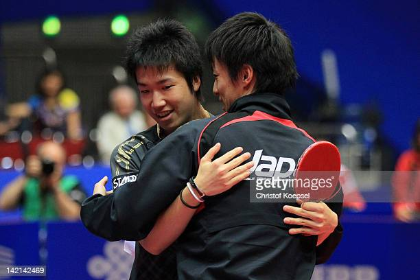 Jun Mizutani of Japan celewbrates his victory with Kenji Matsudaira after winning against Gao Ning of Singapore during the LIEBHERR table tennis team...