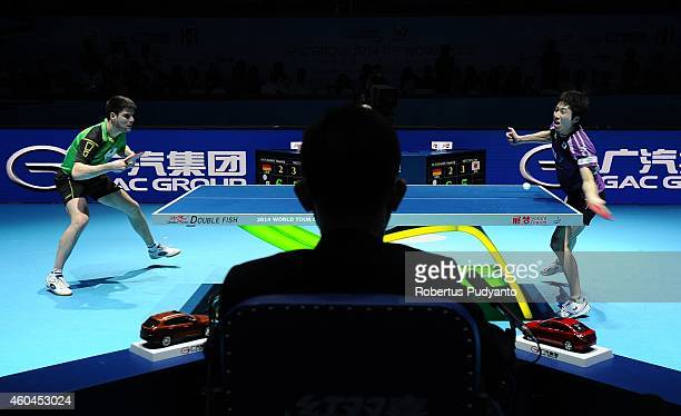 Jun Mizutani of Japan competes against Dimitrij Ovtcharov of Germany during the Men's single final match of the 2014 ITTF World Tour Grand Finals at...