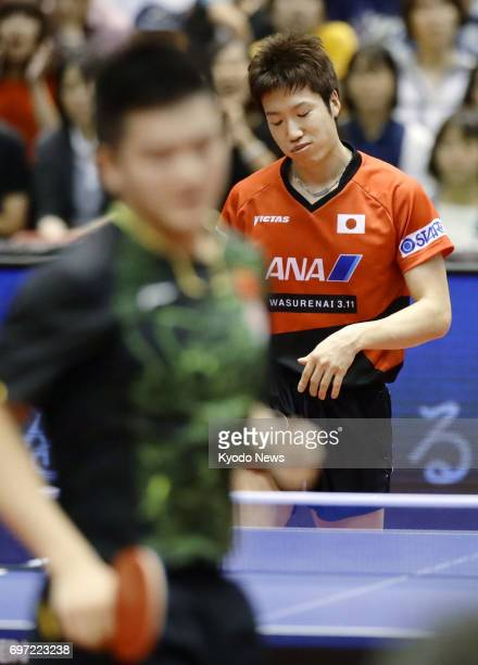 Jun Mizutani of Japan reacts after losing a point during his semifinal match against Fan Zhendong of China at the Japan Open table tennis tournament...