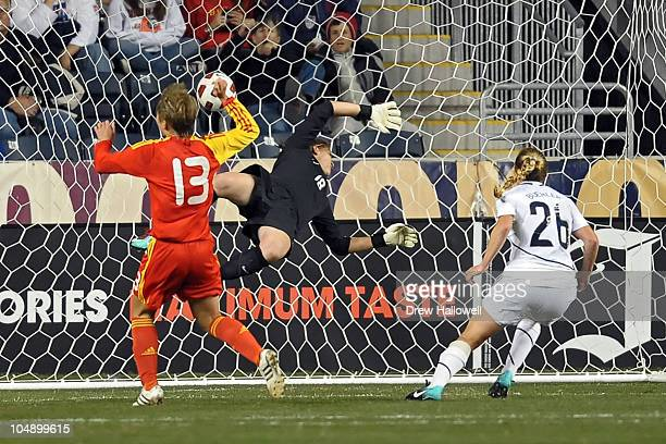 Jun of China scores a first half goal on goalkeeper Nicole Barnhart of the United States as teammate Rachel Buehler watches at PPL Park on October 6...