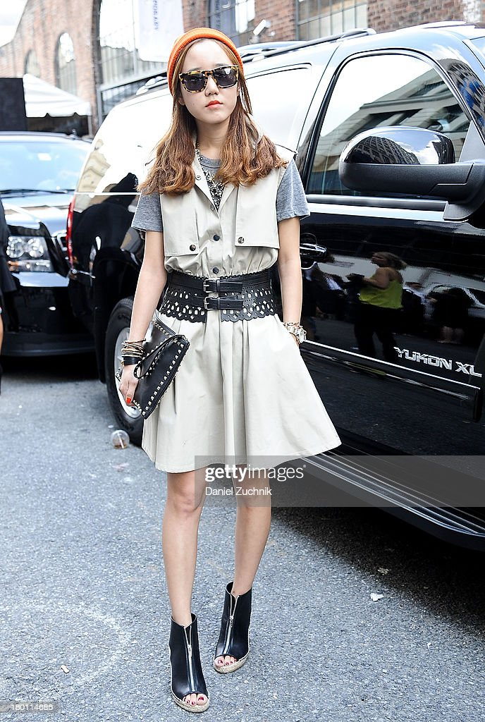 Jun Olivia is seen outside the DKNY show wearing an Opening Ceremony dress, BCBG belt, Valentino bag, Celine shoes, H&M beanie and Karen Walker sunglasses on September 8, 2013 in New York City.
