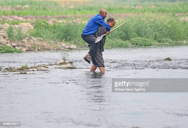 SHIJIAZHUANG June 1 2016 Jia Wenqi right carries his friend Jia Haixia in a river in Yeli Village of Jingxing County north China's Hebei Province May...