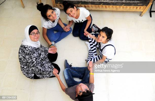 Homeless children sit in a circle with their nanny whom they call mother in their housing unit at the SOS Children's Village for foster care in...