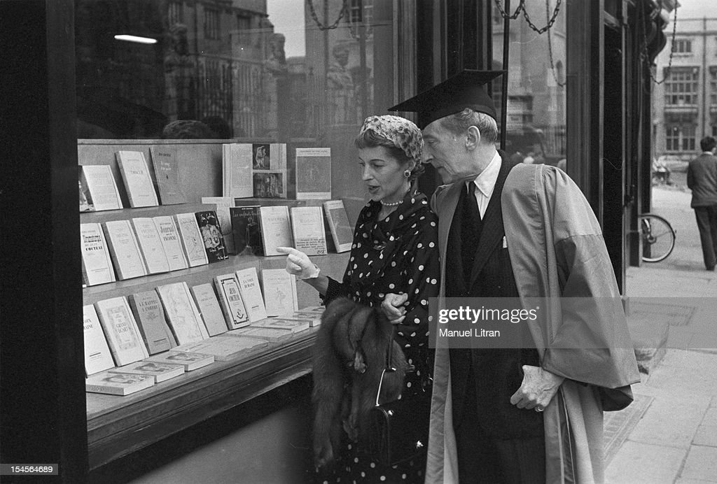 June 14, 1956, the poet and artist Jean Cocteau, Doctor Honoris Causa from the University of Oxford: Jean Cocteau, wearing his graduation gown, the streets of Oxford, accompanied by an unidentified woman in front of the window of a library.