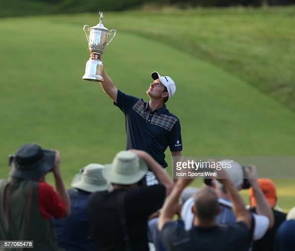 Justin Rose holds the championship trophy high in the air as a crowd of photographer take photos during the fourth round of the 2013 US Open hosted...