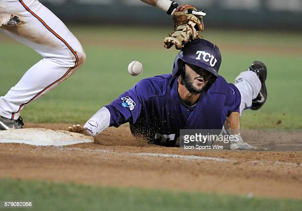 TCU's Garrett Crain dives back into first base after a pickup attempt during the College World Series game between the Virginia Cavaliers and the TCU...