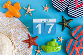 June 17th. Image of june 17 calendar on blue background with summer beach, traveler outfit and accessories. Summer day.