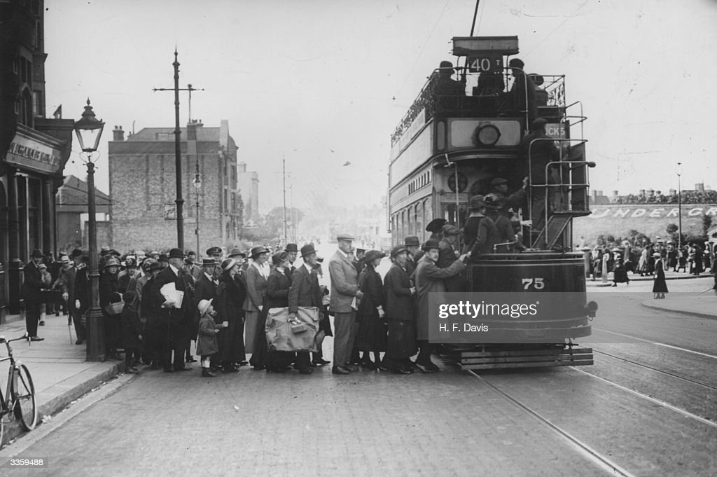 Bank holiday crowds piling onto an open top tram car at Golders Green station London