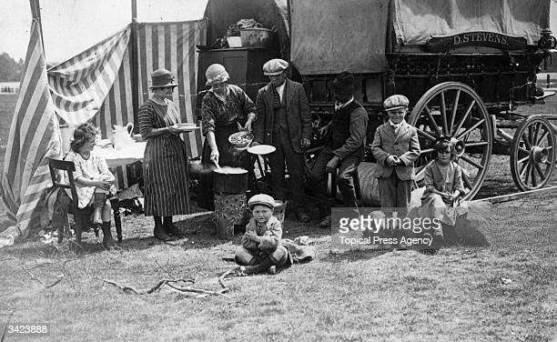 A gypsy family at an Ascot race meeting enjoy a meal outside their caravan