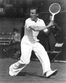 British tennis player Fred Perry swinging for a backhand at Wimbledon