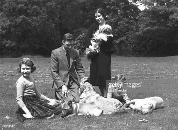 King George VI and Queen Elizabeth with the Royal Princesses Elizabeth and Margaret n the grounds of Windsor Castle with four dogs