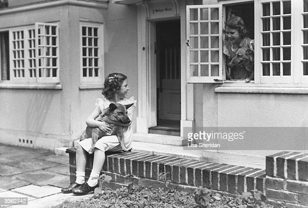 Princess Margaret and her sister Queen Elizabeth II in front of miniature cottage Y Bwthyn Bach in the grounds of Royal Lodge Windsor with two of...
