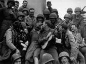 A happy crowd of American soldiers receive a warm welcome from the inhabitants of Cherbourg after its liberation