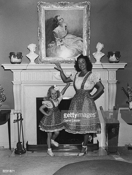 EXCLUSIVE American actor Joan Crawford and her adopted daughter Christina posing at home in front of their fireplace and a painted portrait of...