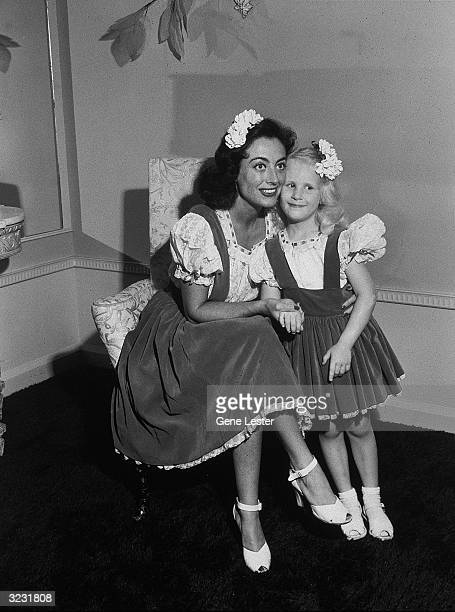 EXCLUSIVE American actor Joan Crawford sits and holds hands with her adopted daughter Christina at their home They wear matching velvet jumpers and...