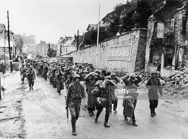 German soldiers are seen here being marched through the streets of Cherbourg France after the city was liberated by the Americans