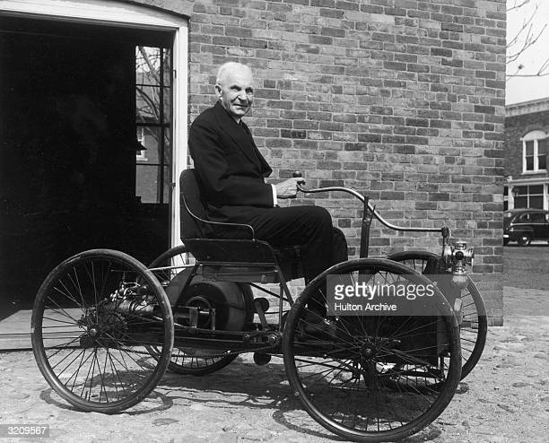 Portrait of American inventor and industrialist Henry Ford sitting in the first automobile he built a 'quadricycle' in front of his former workshop...