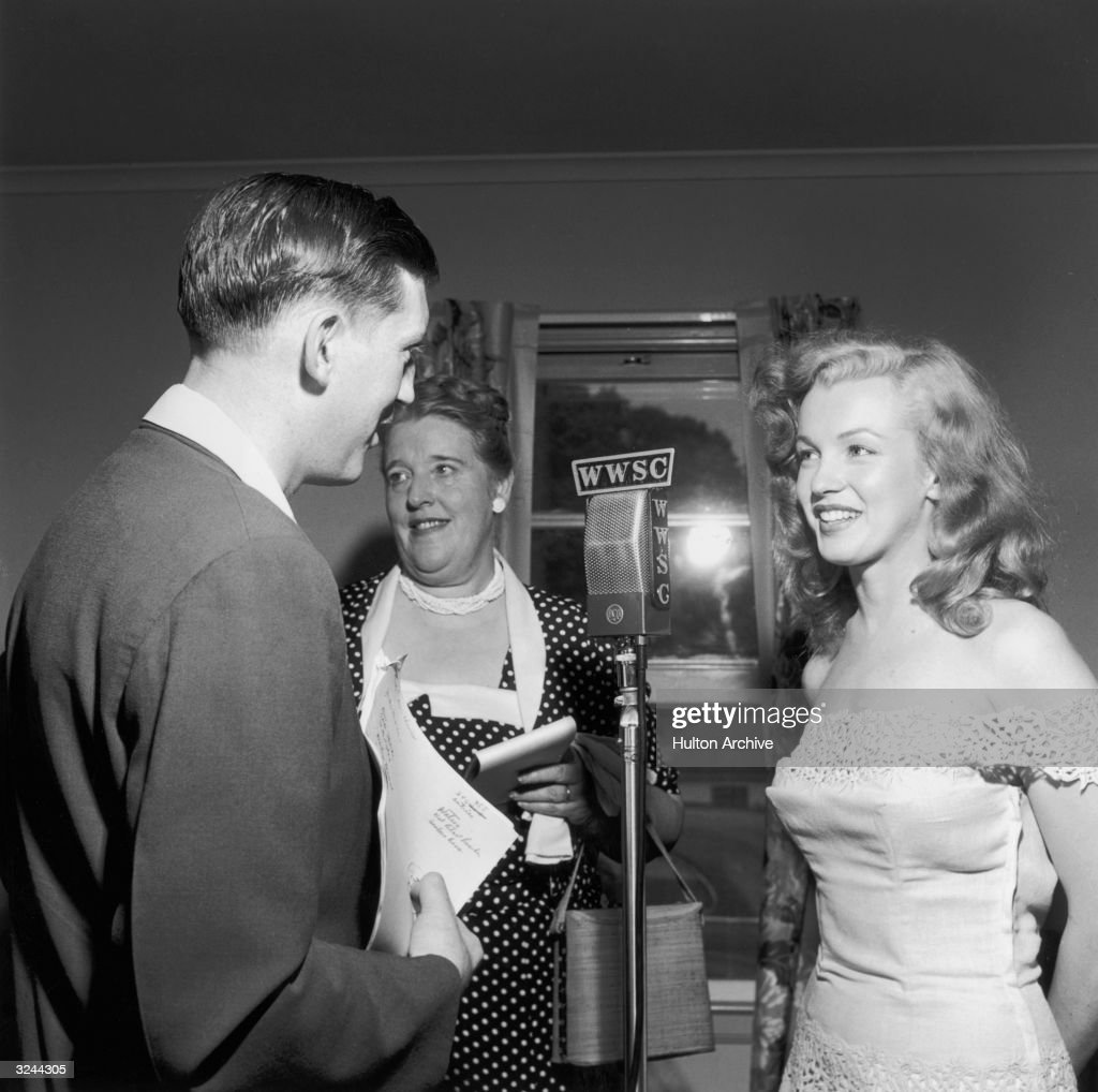 American actor <a gi-track='captionPersonalityLinkClicked' href=/galleries/search?phrase=Marilyn+Monroe&family=editorial&specificpeople=70021 ng-click='$event.stopPropagation()'>Marilyn Monroe</a> (1926 - 1962) stands at a WWSC microphone with a man and woman during a 'Photoplay Magazine' contest event, Williamsburg, New York. Monroe was in New York City to promote her new film, 'Love Happy' and traveled to Williamsburg to present the contest winner with the key to a new house. She is wearing an off-shoulder dress.