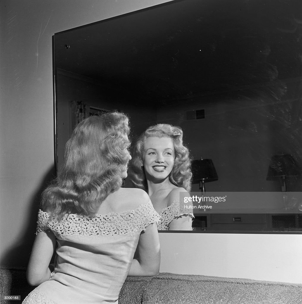 Photoplay magazine sponsored a contest for a 'dream home.' <a gi-track='captionPersonalityLinkClicked' href=/galleries/search?phrase=Marilyn+Monroe&family=editorial&specificpeople=70021 ng-click='$event.stopPropagation()'>Marilyn Monroe</a> (1926 - 1962), promoting her new film Love Happy, took a train to Warrenburg, New York with Don Defore and Lon McAllister to present the contest winner with the keys to the house. The picture shows Monroe smiling in front of a mirror on a wall inside the house, Warrenburg, New York.