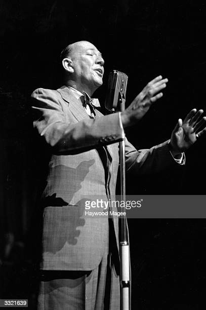 English actor dramatist and composer of light music Sir Noel Coward at the microphone at the 'Stars At Midnight' Charity Show at the London Palladium...