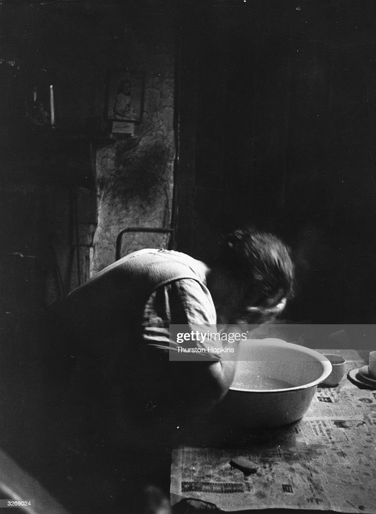 A woman washing her face over a basin in her run-down Liverpool home. Original Publication: Picture Post - 8995 - Liverpool Slums - pub. 1957