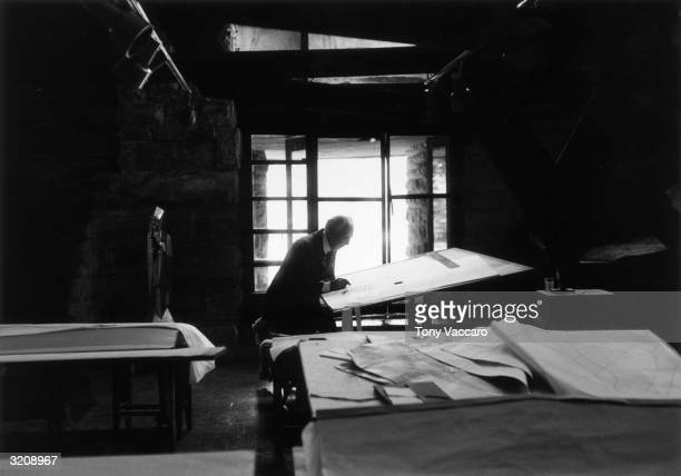 American architect Frank Lloyd Wright working on designs while sitting in front of a drafting table in his studio at Taliesin West Arizona