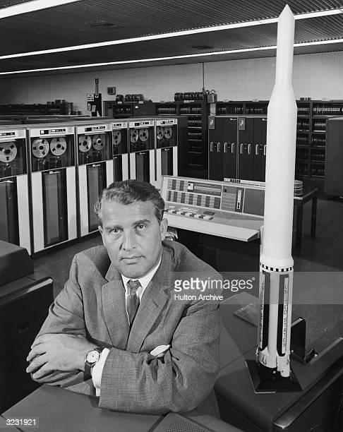 German rocket engineer Wernher Von Braun sitting next to a rocket model and a mainframe computer in Huntsville Alabama