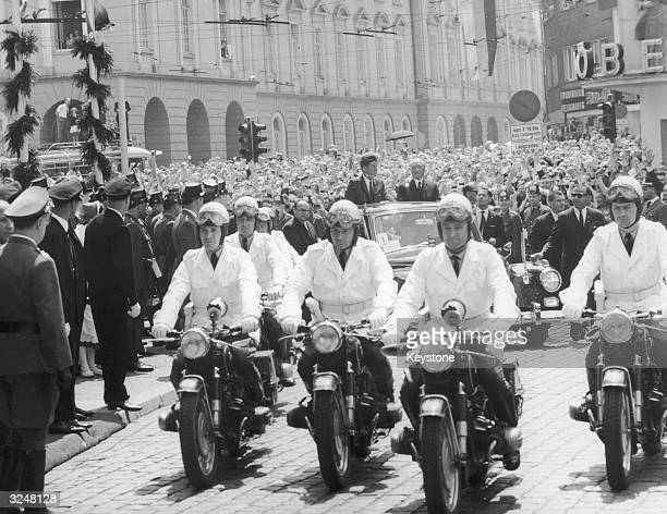 Motorcycle outriders lead the motorcade of American President John F Kennedy on a tour of Berlin with West German chancellor Konrad Adenauer