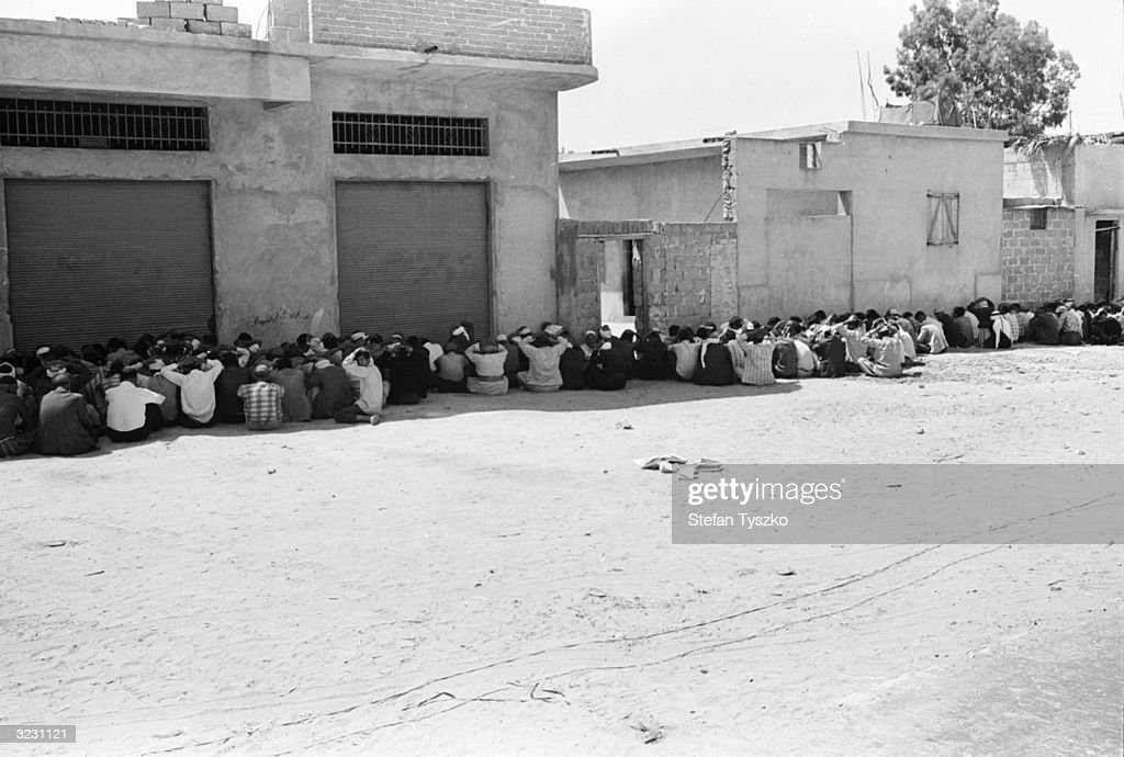 People huddling against the wall having been caught breaking the Israeli enforced curfew in Gaza during the Six Day War Mass arrests follow