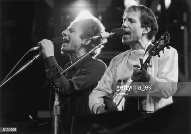 American musicians Art Garfunkel and Paul Simon of the folk duo Simon and Garfunkel perform during a reunion concert at Wembley Stadium London England