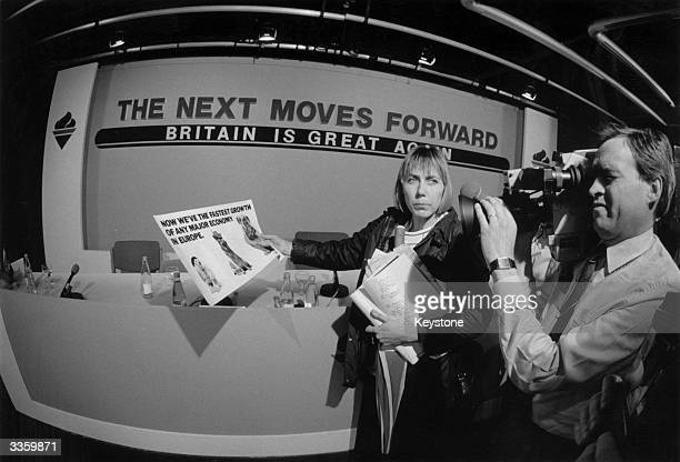 Broadcast journalist Eleanor Goodman holds a cue card up to a video camera unit at the Conservative Party electoral press conference