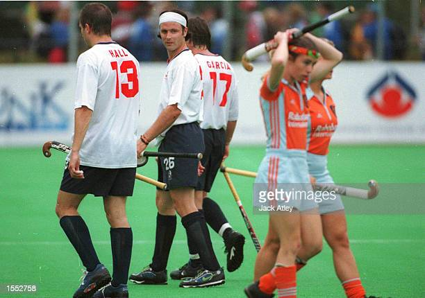 England's Calum Giles admires two of the Netherlands team members as he leaves the pitch following England's loss to Korea at the Sate Hockey Centre...
