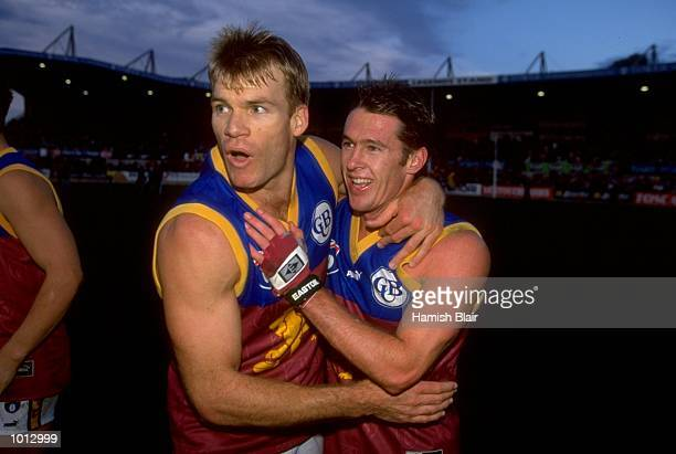 Richard Champion and Craig McRae of Brisbane celebrate following the AFL Round 11 match between the Carlton Blues and the Brisbane Lions played at...