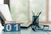 June 1st. Day of the month 1 , wooden color calendar on business workplace background. Summer concept. Empty space for text.
